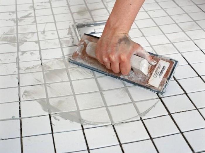 Затираем швы между плиткой. | Фото: deodom.ru.
