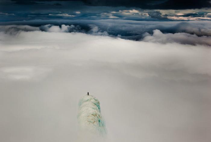 Альпинист, стоящий на вершине горы в Исландии.