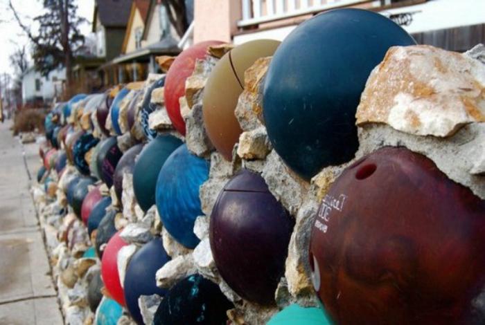 Забор, украшенный шарами для боулинга.