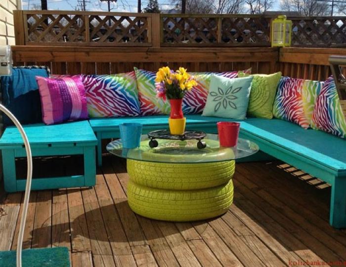 Столик из старых шин, покрашенных в яркий цвет и круглого стекла.