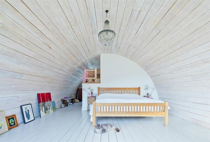Светлая спальня, оборудованная в мансарде.