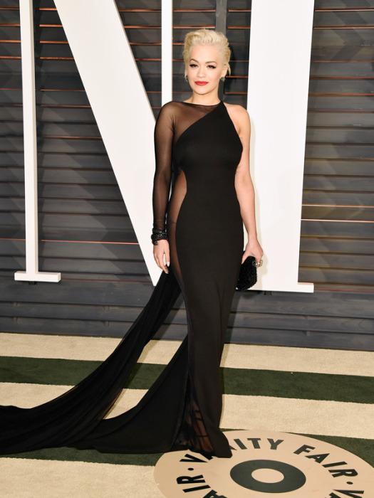 Рита Ора в элегантном черном платье со шлейфом и очень откровенными прозрачными вставками по бокам.