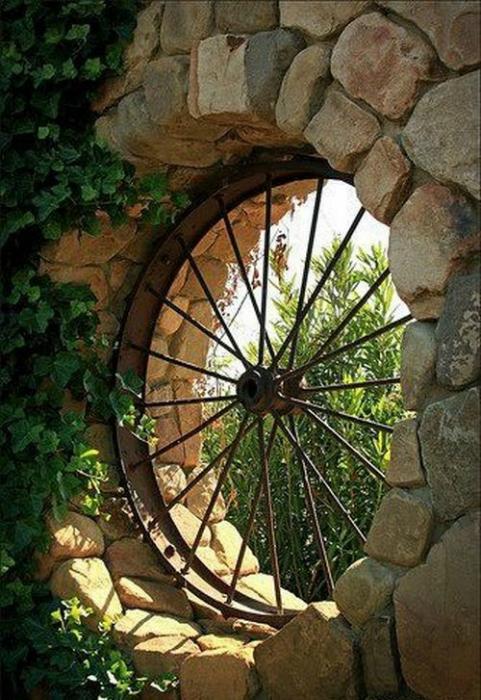 Окно в сад из старого колеса от телеги.