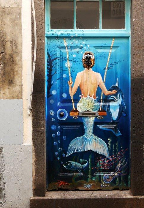 Обыкновенная деревянная дверь, украшенная картиной с изображением прекрасной русалки.