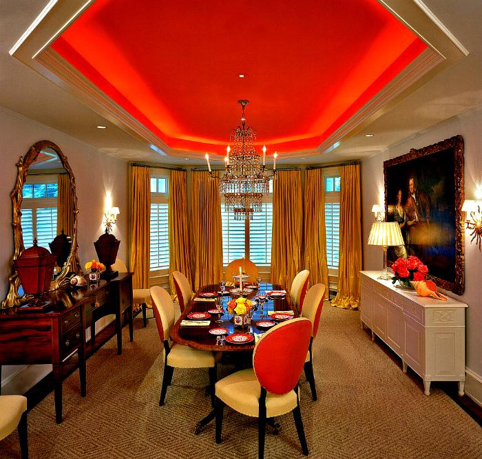 Навесной потолок оранжевого цвета и классическая люстра.