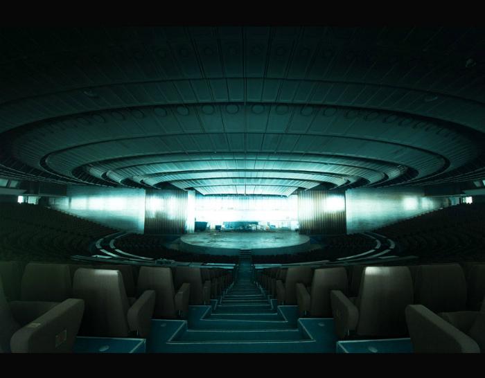 Заброшенный культурно-спортивный комплекс в Таллине, освещенный таинственной полоской света, который проникает сквозь маленькие окна.