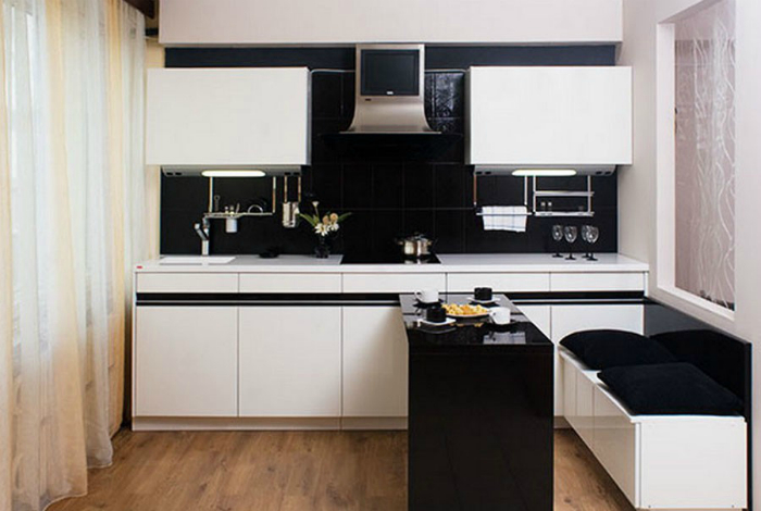 Маленькая кухня, выполненная в черно-белом цвете, с выдвижным обеденным столом.