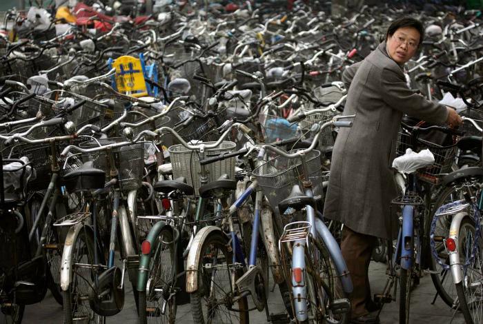 Женщина забирает свой велосипед с велопарковки. | Фото: bublink.ru.