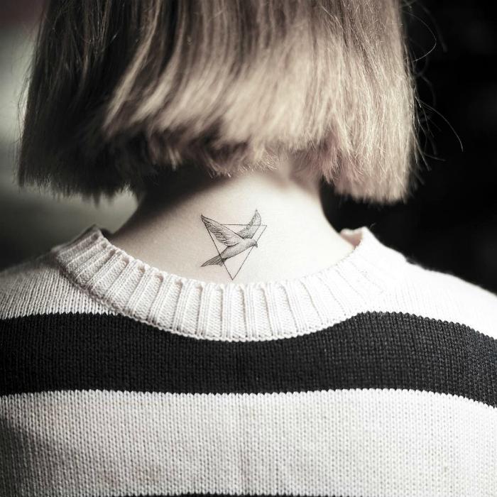 Минималистичное тату с изображением птицы в треугольнике на девичьем затылке.