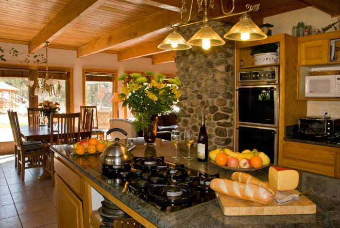 Уютная кухня в деревенском стиле с деревянной мебелью и каменной отделкой стен.