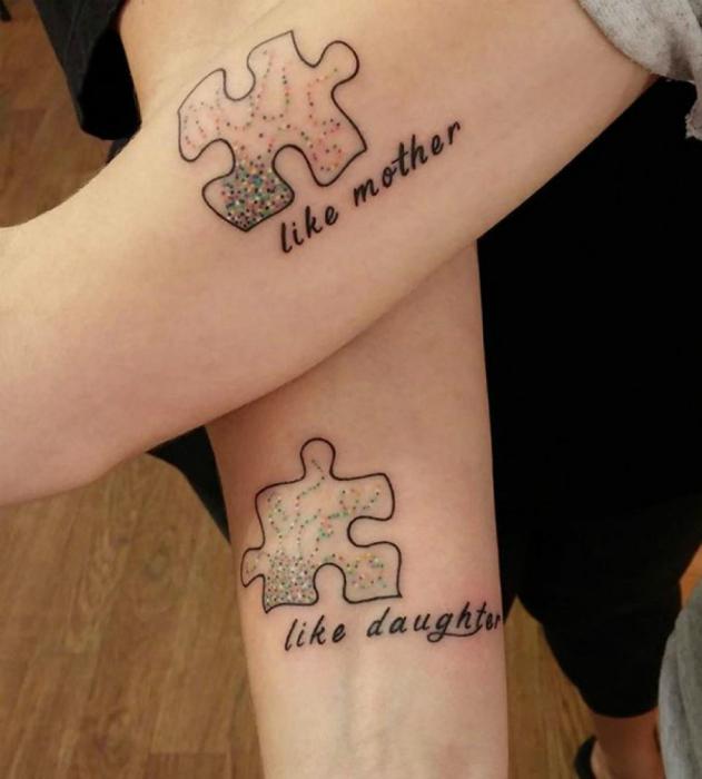 Татуировки с изображением кусочков пазла на руках у дочки и матери.