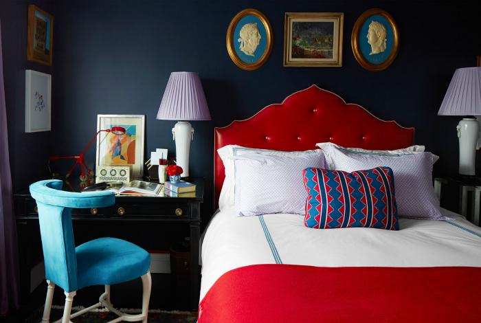 Спальня с темными стенами и красной кроватью.