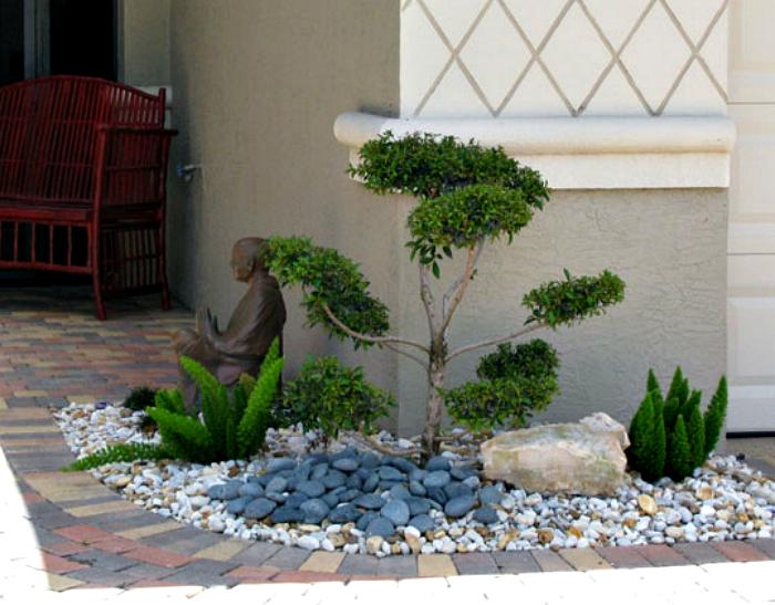 Крошечная клумба с растениями и галькой.