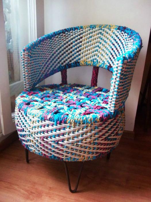 Оригинальное плетеное кресло из старой автомобильной шины, грубых разноцветных ниток и металлических прутьев.