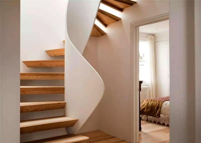 Лаконичная деревянная лестница с извилистыми перилами.
