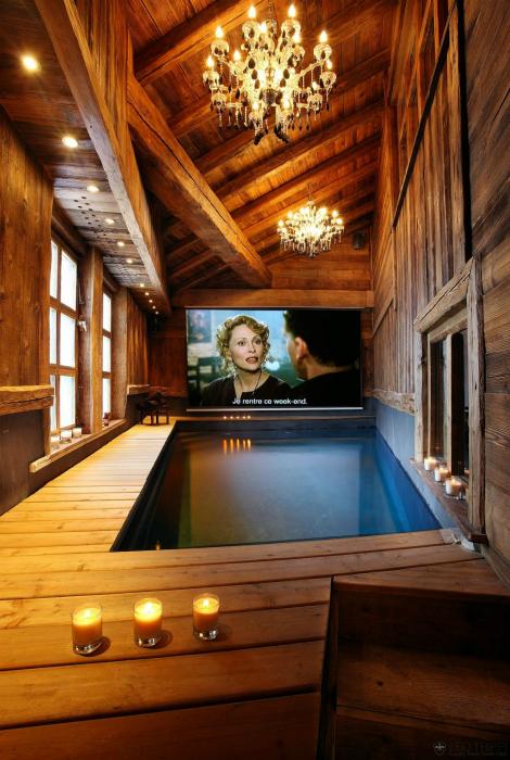 Небольшая комната для отдыха с бассейном и огромным телевизором.