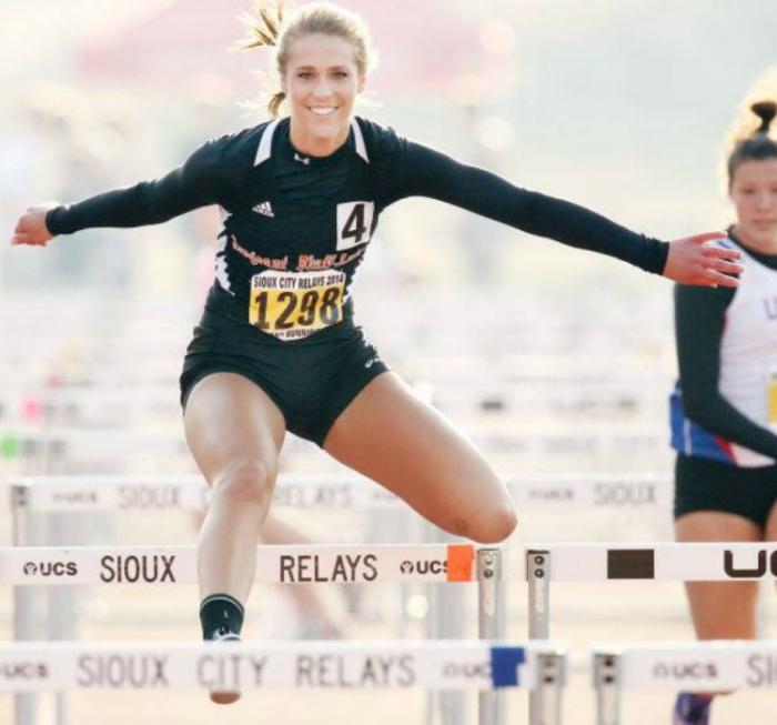 С широкой улыбкой, девушка перепрыгивает барьер на соревнованиях в Сиу Сити.