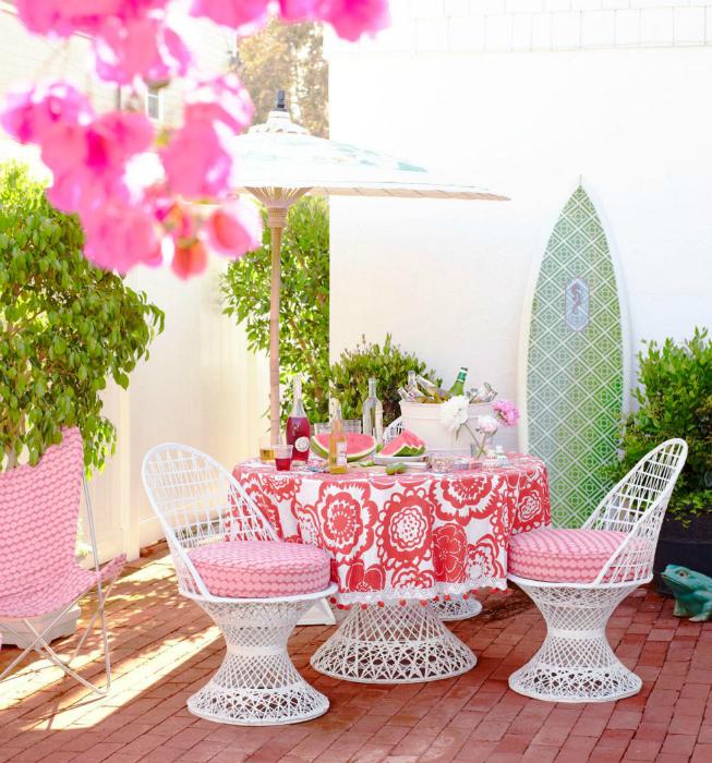 Патио с плетенной мебелью и ярким текстилем.