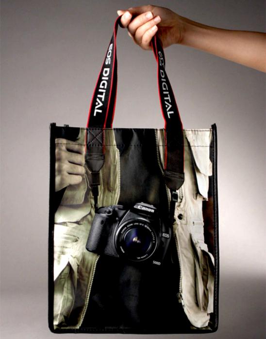 Сумка з щільним рекламним ремінцем і зображенням фотоапарата Canon.