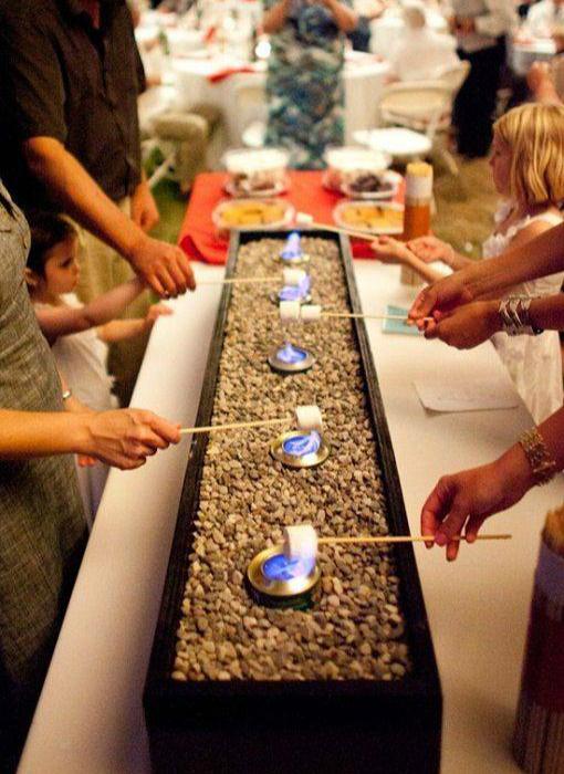 Насыпьте в поддон камешков и поставьте туда несколько металлических горелок. Гости смогут самостоятельно жарить на них зефир, фрукты или сыр.