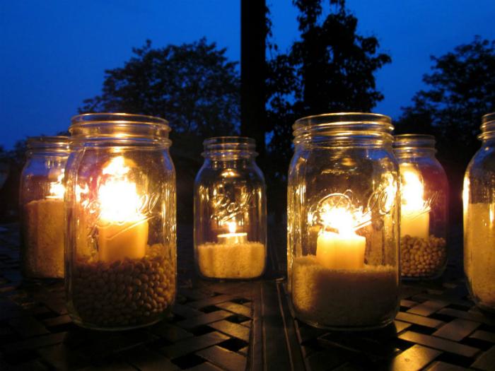 Возьмите баночки разных размеров, насыпьте туда крупы, камешки или песок и поставьте туда свечи. Ваш сад будет выглядеть волшебно, в свете множества фонариков.