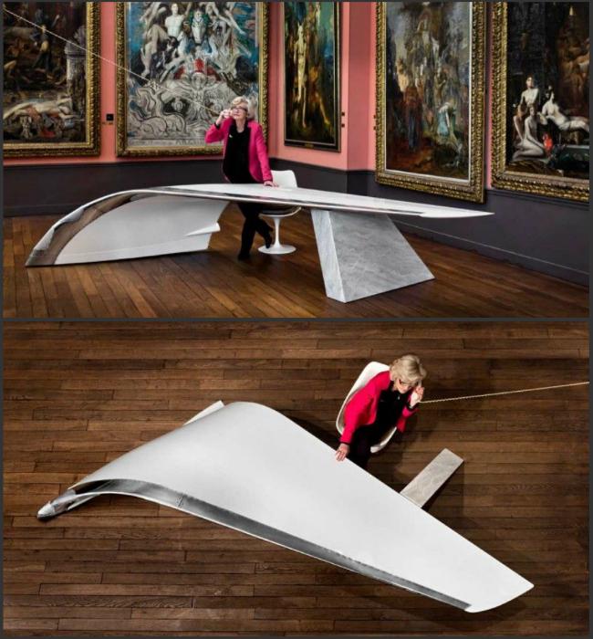Четырехметровый стол опирается на гранитный блок цвета морского жемчуга. По замыслу разработчиков, сочетание алюминиевого крыла и серого гранита метафорически отражает две стихии – воздух и землю.