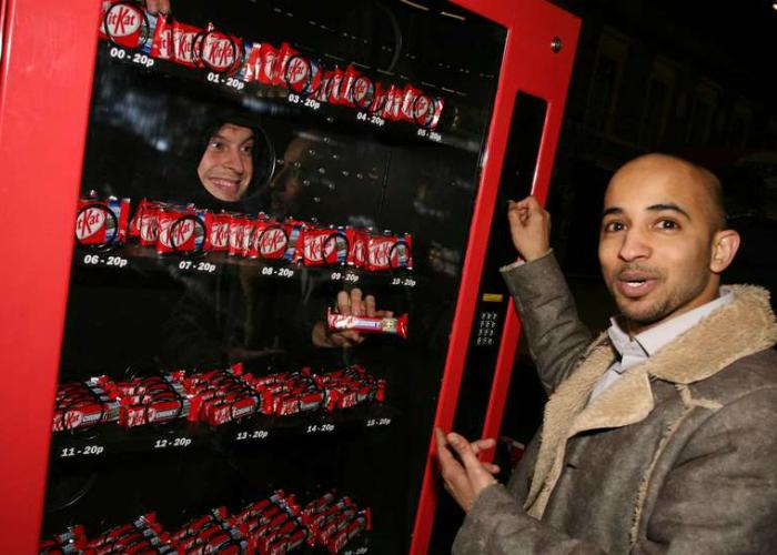 В Лондоне расположен новый дружелюбный торговый автомат от компании Nestlе. Его главной особенностью является то, что товар покупателям выдает не бездушный кусок железа, а живой человек. Создатели решили, что приятный разговор с веселым продавцом это отличный бонус к купленному Kit Kat.
