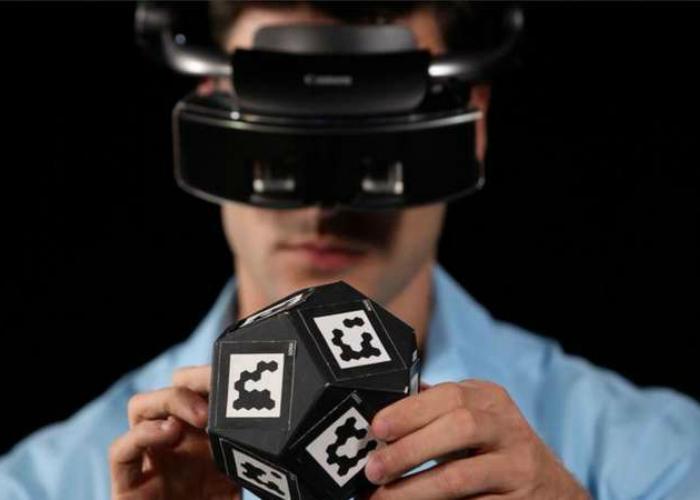Закрепив массивное устройство на голове, пользователь получит возможность видеть виртуальные объекты наряду с реальными. Такая разработка  поможет дизайнерам и архитекторам накладывать свои изображения на трехмерные макеты.