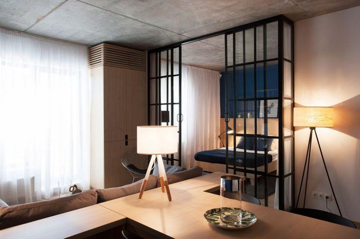 Бетонные потолки отлично сочетаются с синим цветом и мебелью из белого дерева