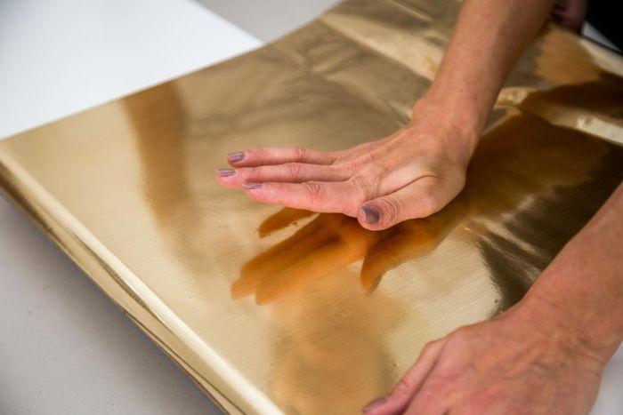 Белые полки декорировали золотистой бумагой
