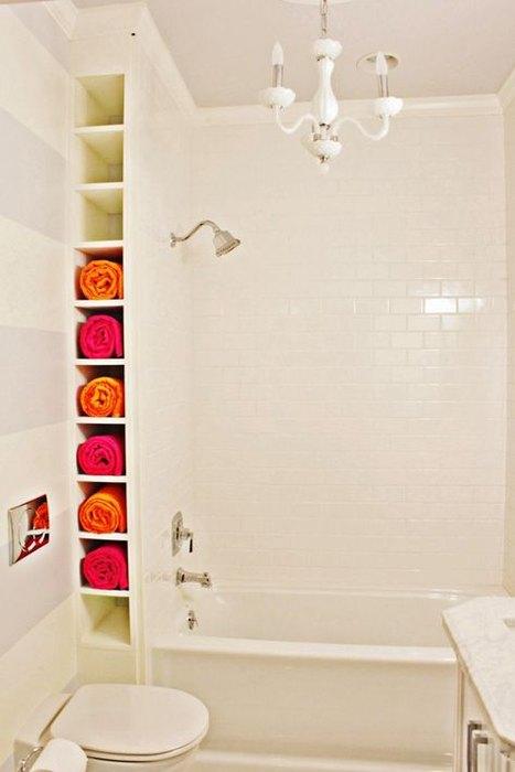 Яркие полотенца делают интерьер белой ванной интересным