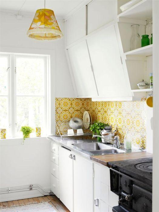 Жёлтый кухонный фартук перекликается со светильником по цвету