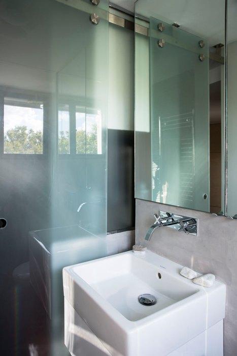 Стеклянная перегородка и зеркало зрительно увеличивают маленький санузел