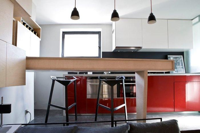 Барная стойка выполняет роль зонирующего элемента, столовой и системы хранения
