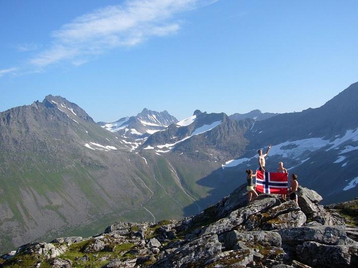 Туристы с норвежским флагом после восхождения на гору.