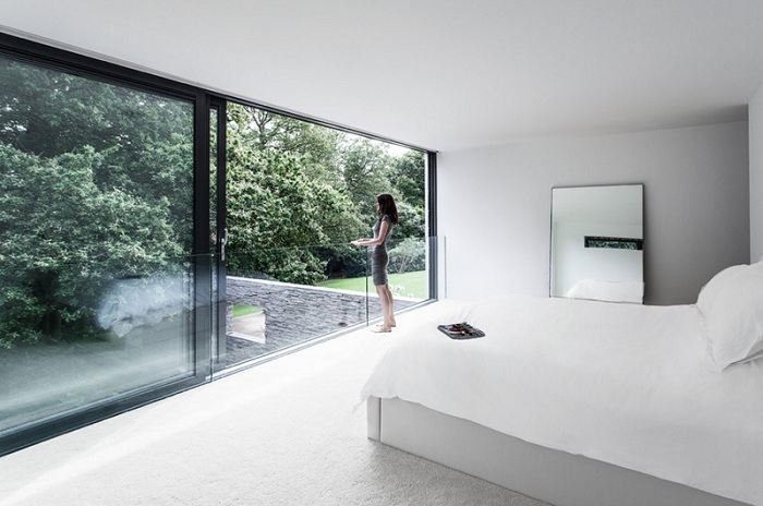 Удивительная белая спальня с раздвижными дверьми от студии AR Design Studio Ltd.