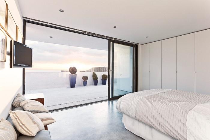 Шикарный вариант оформления спальни в светлых тонах с огромными раздвижными стеклянными дверьми, которые выходят на балкон.