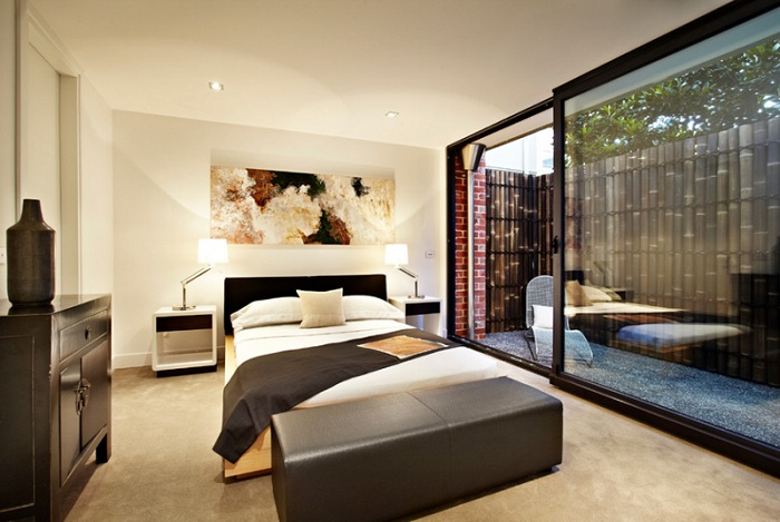 Интересный вариант декорирования спальни и возможного выхода на балкон, стеклянной раздвижной дверью.