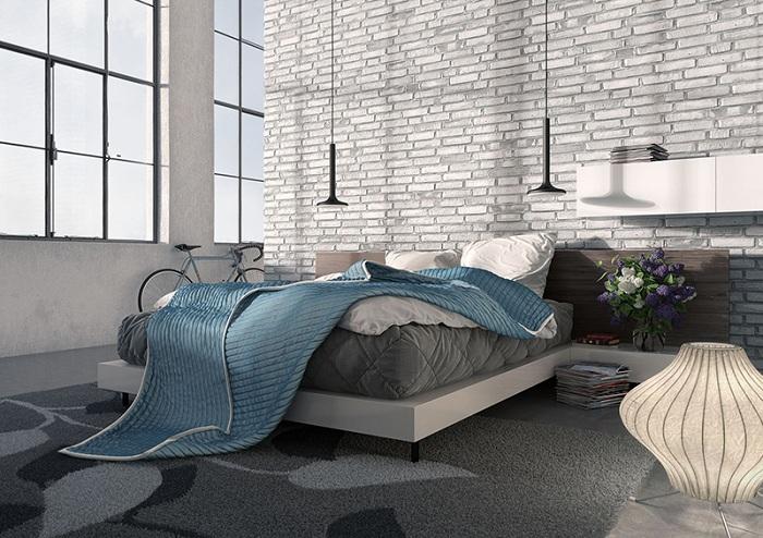 Спальня с высоким потолком залита естественным светом в серо-белых тонах.