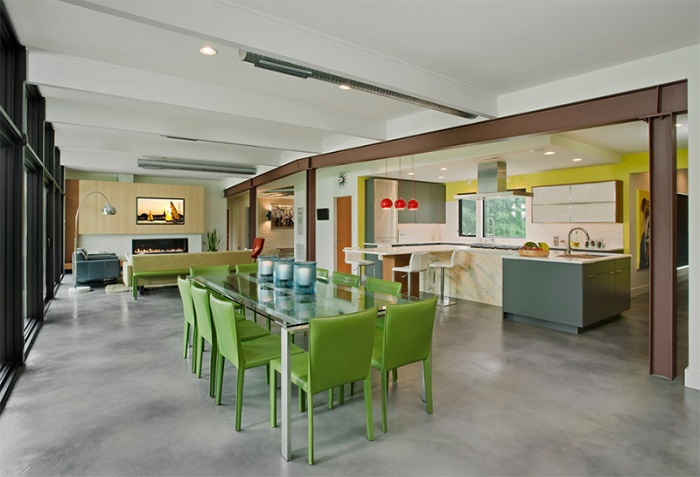 Просторный дом с открытой планировкой, где есть обеденная зона с симпатичными зелеными стульями, кухня и гостиная объединены.
