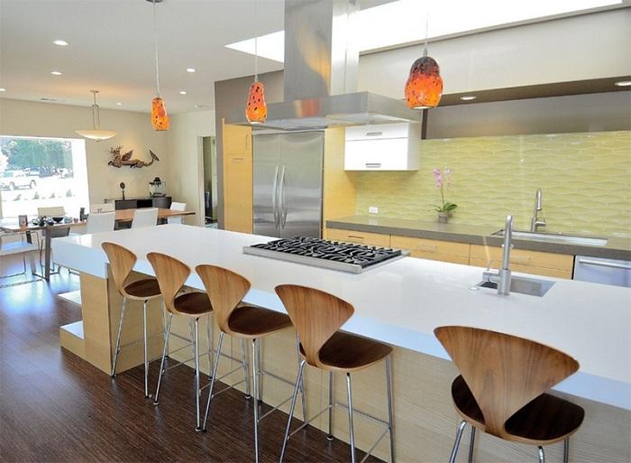 Современный дизайн кухни с оранжевыми подвесными светильниками.