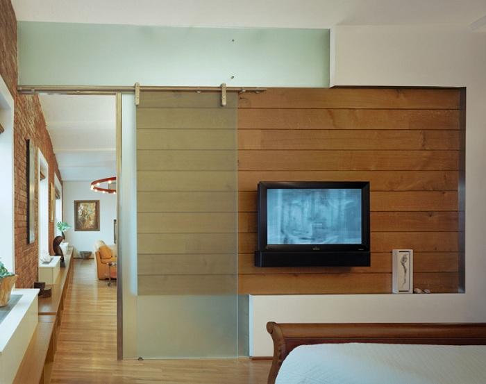Симпатичный интерьер спальной создан благодаря особенной двери раздвижного типа.