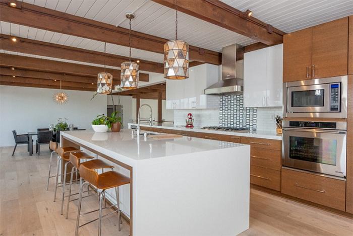 Кухонное пространство оформлено в белых тонах с добавлением древесины, что просто и отлично подчеркивает особенность стиля.