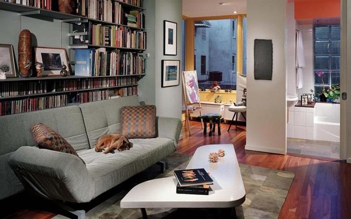 Небольшой столик нестандартной формы и книжные полки создают художественный интерьер в крохотной гостиной.