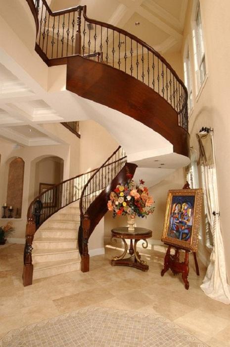 Богатый интерьер комнаты подчеркнут симпатичной лестницей из дерева в Средиземноморском стиле.