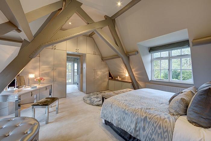 Спальня оформлена в светлых тонах и дополнена необычными стойками, которые поддерживают потолок.