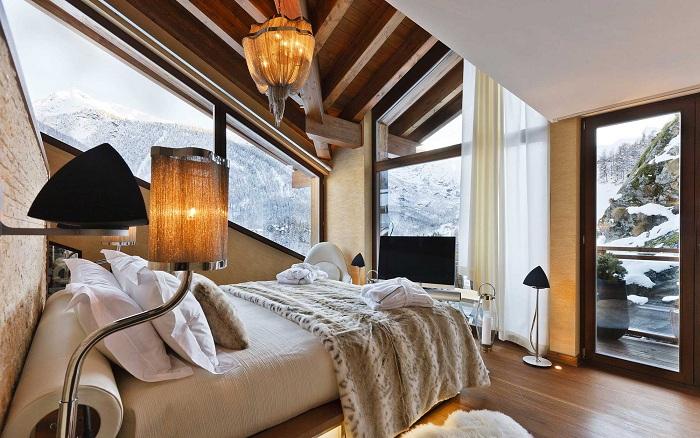 Теплая и уютная атмосфера спальной комнаты с красивым зимним видом из окна порадует глаз.