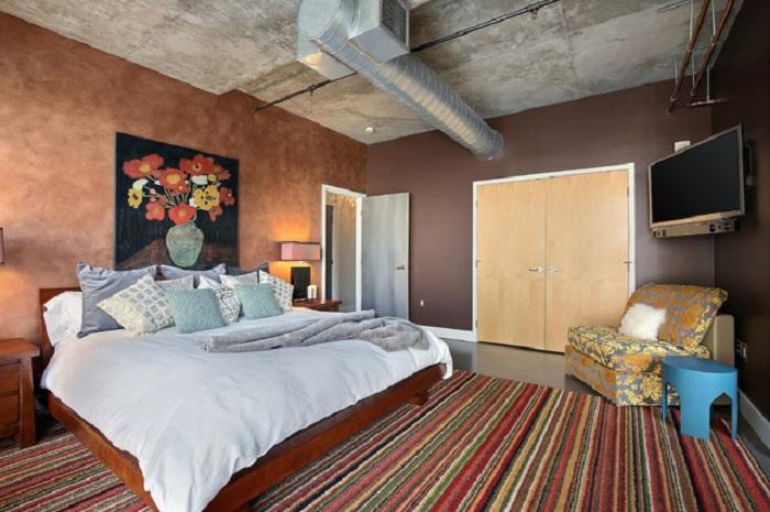 Спальня с нестандартным потолком, который в свою очередь ярко показывает особенности промышленного стиля в интерьере.