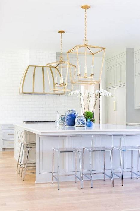 Светлая белоснежная кухня очень красиво смотрится с нестандартными люстрой и вытяжкой.
