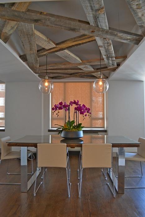 Нестандартный интерьер столовой создан при помощи деревянных перекладин на потолке.